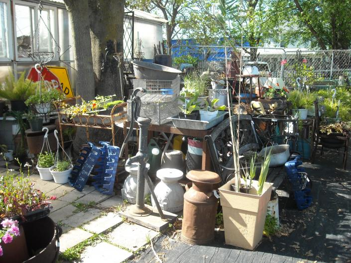 old water pump on wooden base , lots of asst concrete pots, milkcans , benches and more